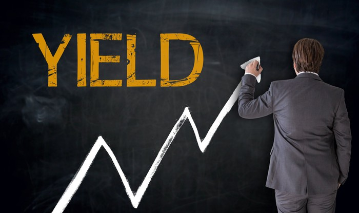 "Businessman drawing line going up on chalkboard next to the word ""yield"""
