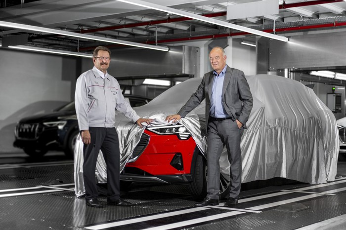 Patrick Danau and Peter Koessler standing at the end of an automotive assembly line, with a vehicle under a show-car-style cover. One corner of the cover is lifted to reveal the front of a red Audi SUV.