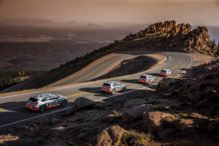 Four Audi e-tron prototypes, in their distinctive black-white-orange camouflage, are shown heading downhill on a winding mountain road.