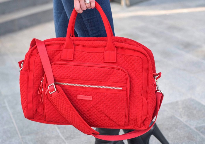 A person holding a red Vera Bradley bag.