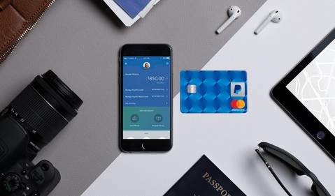 PayPal app displayed on smartphone with a credit card lying next to it.