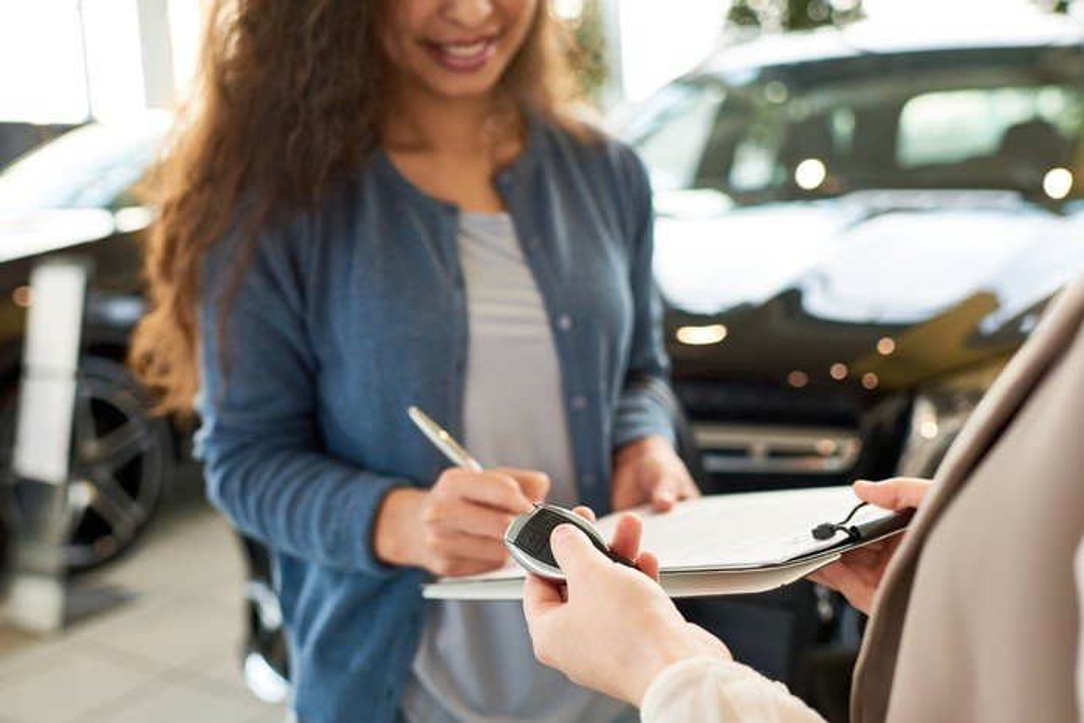 Woman signing paperwork at car dealership.
