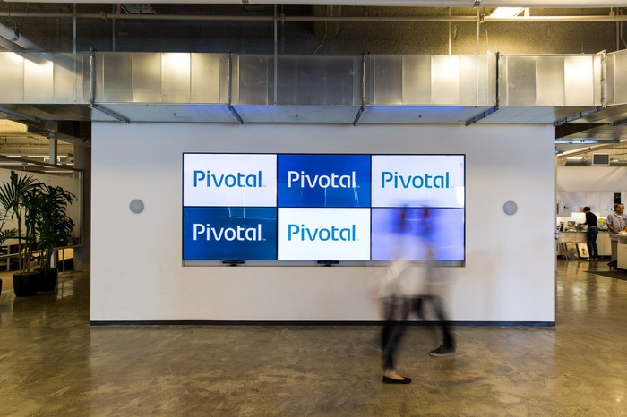 The Pivotal logo on screens within an office.