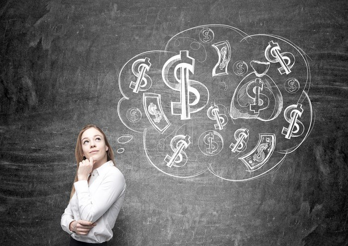 Woman with thoughtful expression in front of a chalkboard thought balloon containing dollar signs