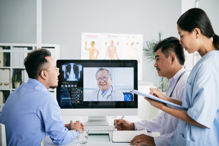 A group of medical interns interacts with a doctor on a monitor.