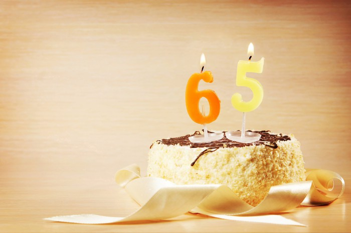 Cake with lit candles in the shape of the numbers 6 and 5 on top.
