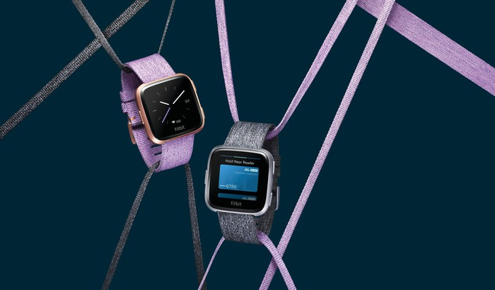 Two versions of the Fitbit Versa hanging from strings.