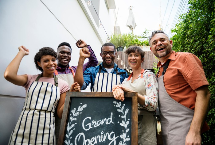 People are happy in front of a grand opening sign.