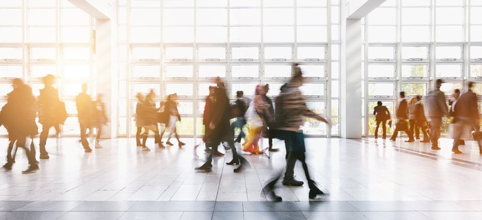 A blurred image of people walking through an airport.