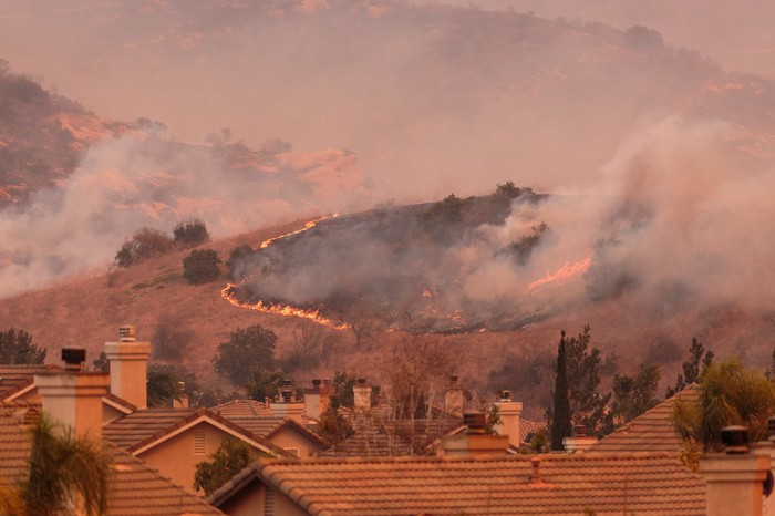 Wildfire rushing down hill towards houses below