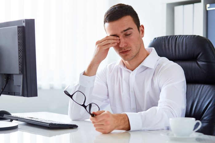 Man at desk rubbing his eyes while holding glasses