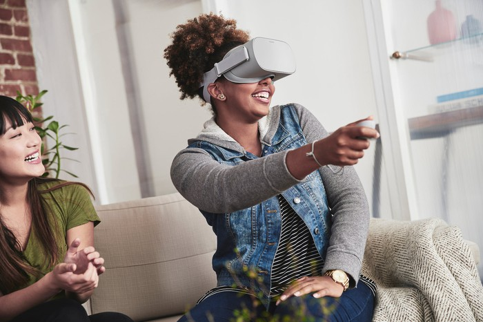 Woman sitting on a couch while using Oculus Go