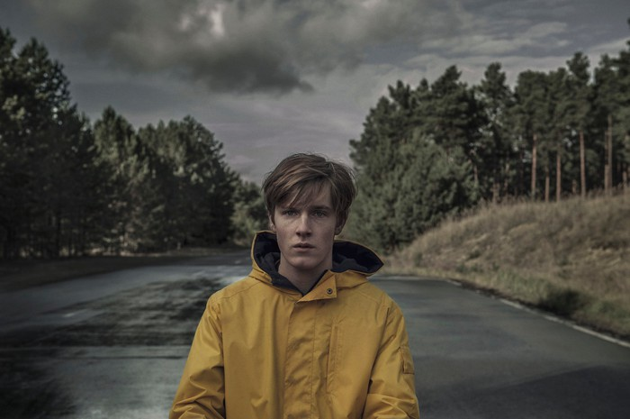 A person standing on a road in a yellow raincoat in a scene from Netflix original Dark.