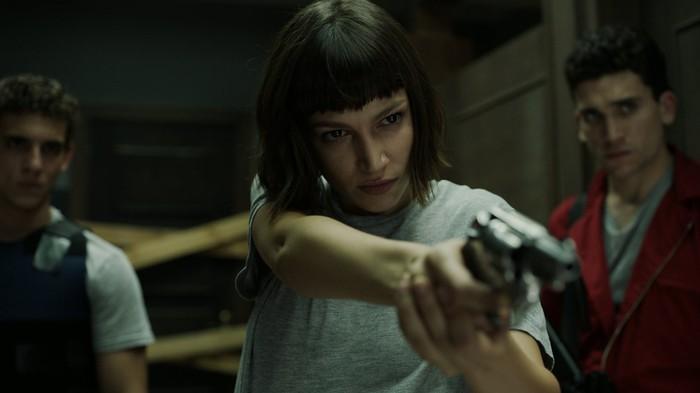A woman pointing a gun at an unseen foe as two men look on in Netflix original La Casa de Papel (Money Heist).