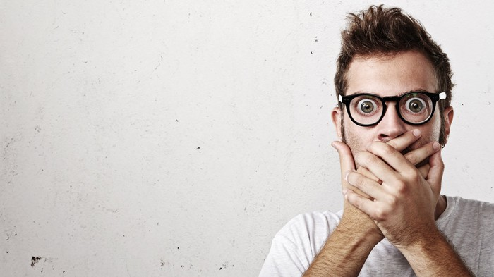 Surprised man with bulging eyes and hands over mouth
