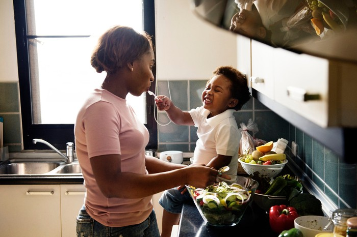 Woman standing near a kitchen counter preparing a fresh salad while a toddler sitting on the counter smiles and puts a spoon in the woman's mouth