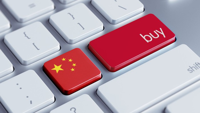 Two red buttons on a white computer keyboard, one with the Chinese flag and the other the word buy.