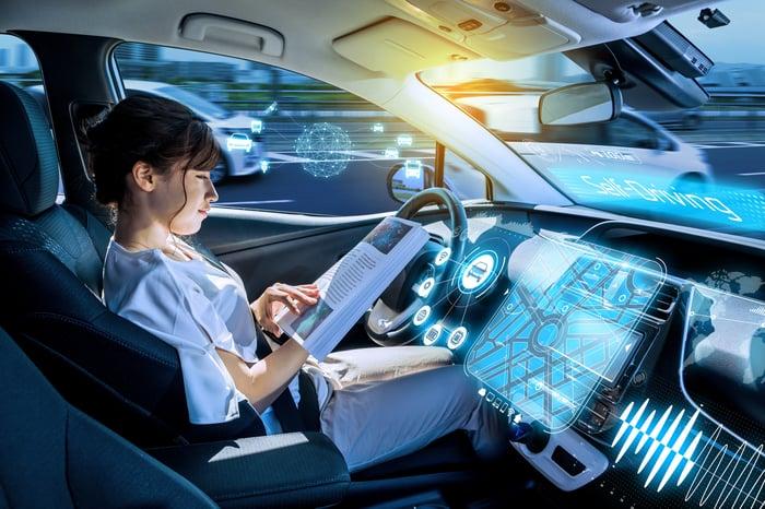 A woman sits in a driverless car.