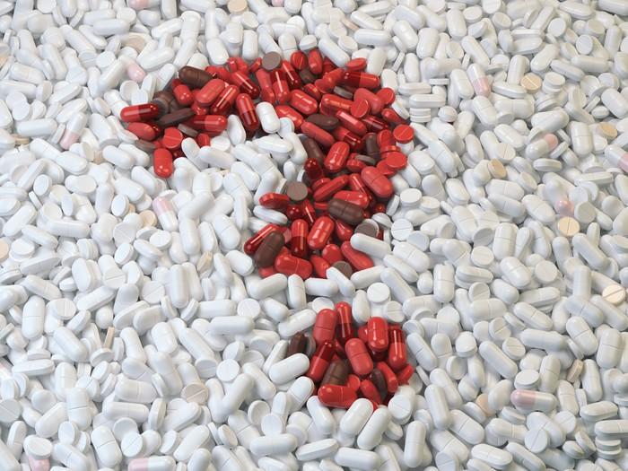Red pills forming question mark in pile of white pills