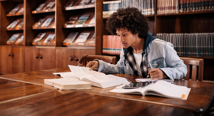 Male college student studying at a table with several books open.