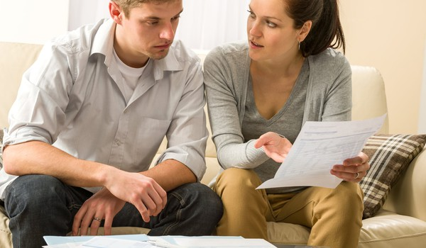 young couple looking over documents looking worried taxes finances