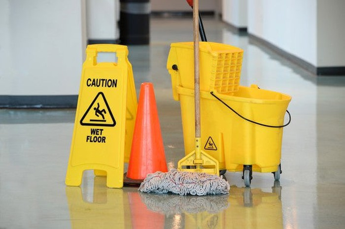 Yellow mop and caution sign next to a yellow bucket, with an orange cone in the middle