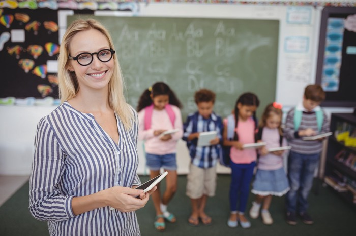 school teacher standing in front of students and holding tablet