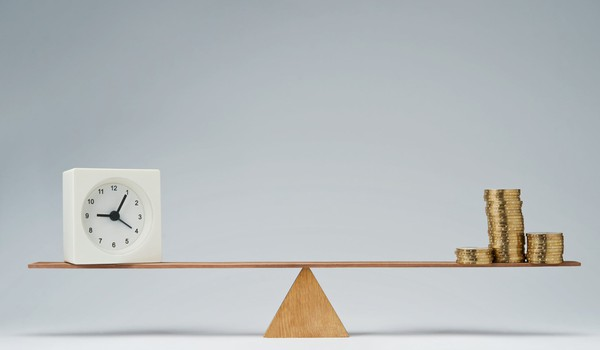 seesaw with clock on one end and stacks of coins on the other -- time money balance scale