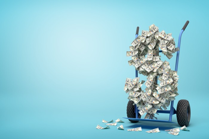 A hand truck moving a large dollar sign shape made of floating dollar bills.