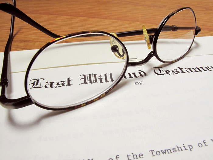 Last will and testament with a pair of eyeglasses sitting on top.