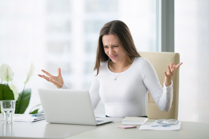 Woman gesturing and staring at laptop screen with disgusted expression.