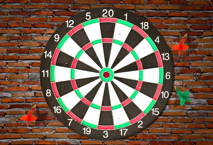 Three thrown darts that have all missed the dartboard.
