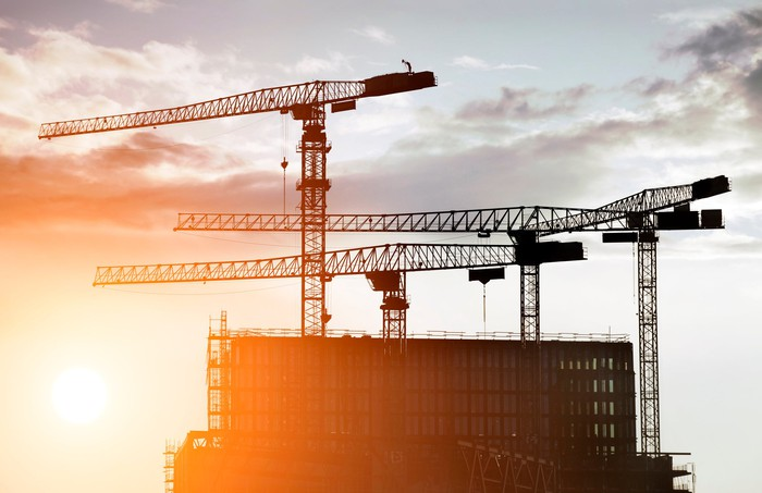 The sun rising behind a building with cranes surrounding it.