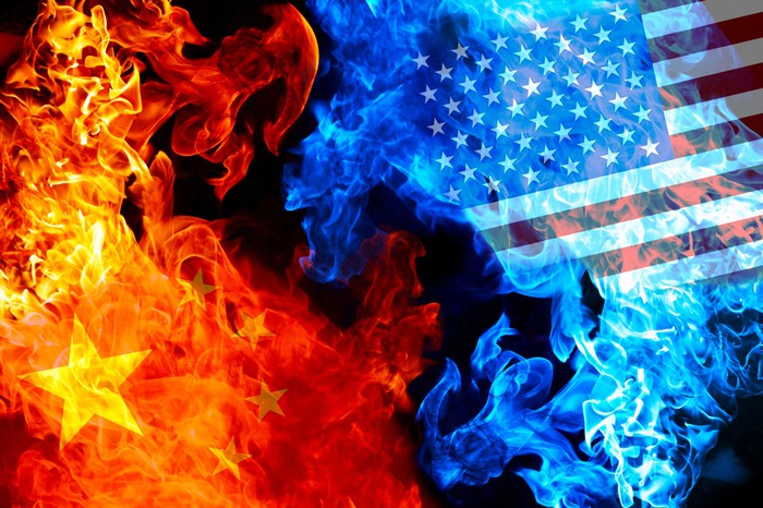A Chinese flag projected on flames and a U.S. flag projected on smoke.