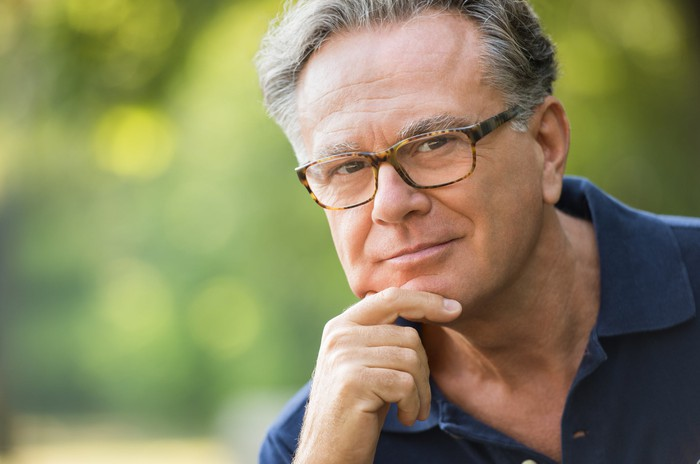 A bespectacled man in his early 60s in deep thought, with his hand on his chin.
