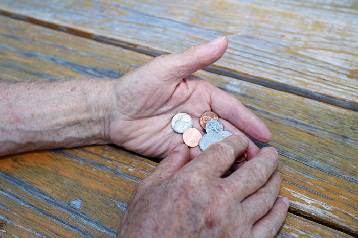 Senior holding a bunch of coins