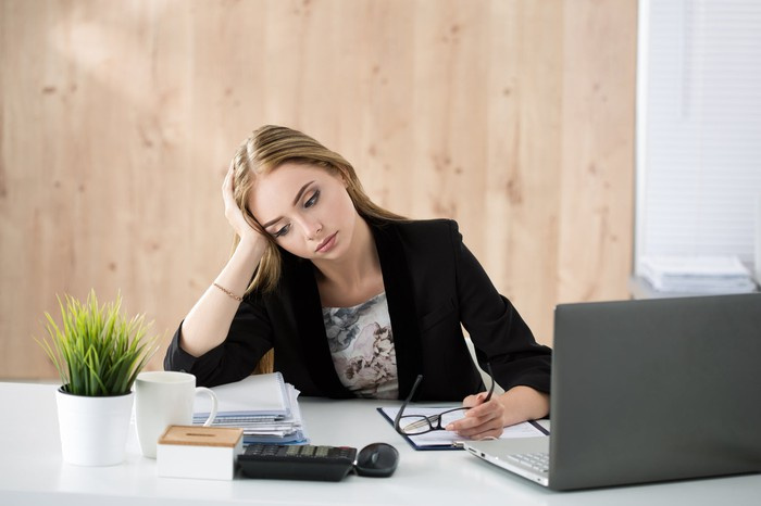 Woman leaning at a desk as if bored