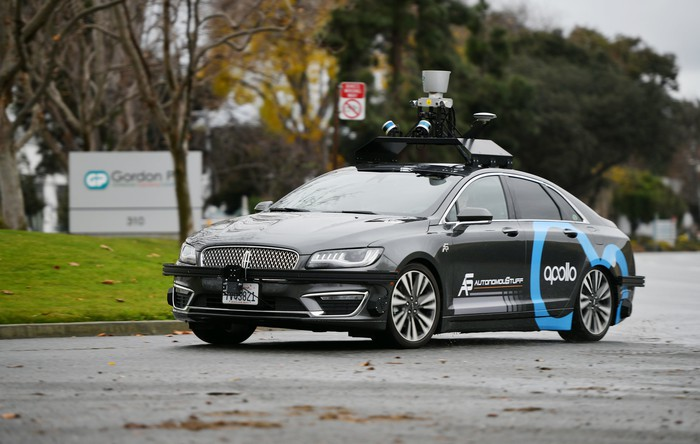 A self-driving car with numerous sensors on the roof and the Apollo logo on the door.