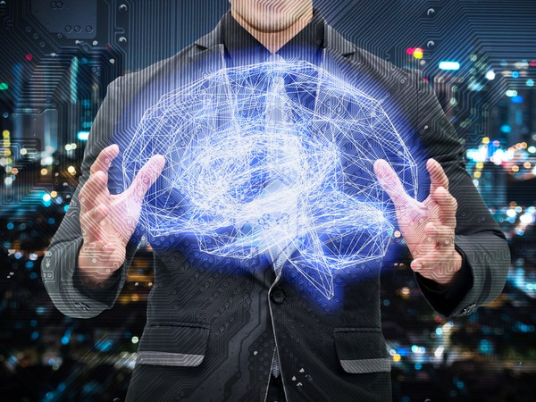 Man in a suit holding a wireframe brain connected to an  electronic circuit graphic with a bokeh city background