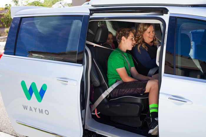 Numerous riders smiling in a mini-van with the Waymo logo on the door.