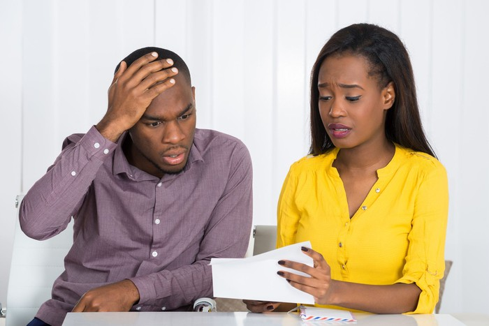 Couple looking at paperwork in dismay, with the man touching his forehead with his right hand.