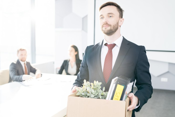 A man carrying a box of office supplies and leaving a room with two colleagues watching him.