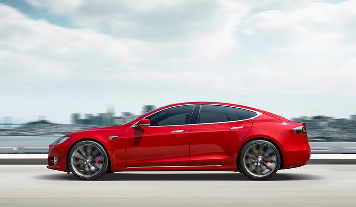 A red Tesla Model S luxury sedan driving down a road.