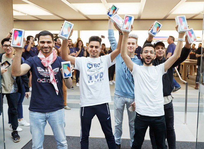 Apple customers holding new iPhone X devices on launch day