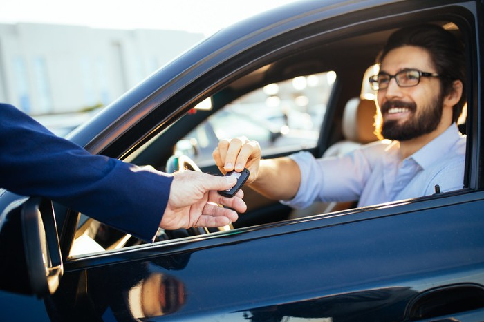 Man in car being handed key by another person.