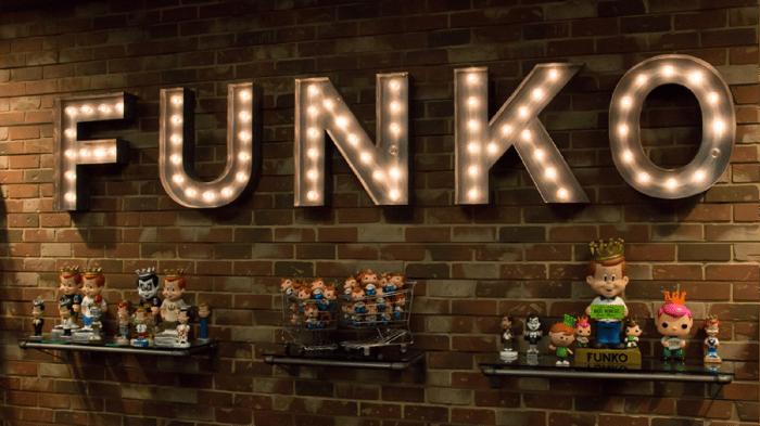 Funko illuminated sign with Funko dolls on shelves.
