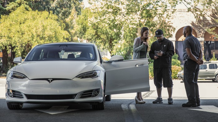 A woman checking in a white Model S to a Tesla employee