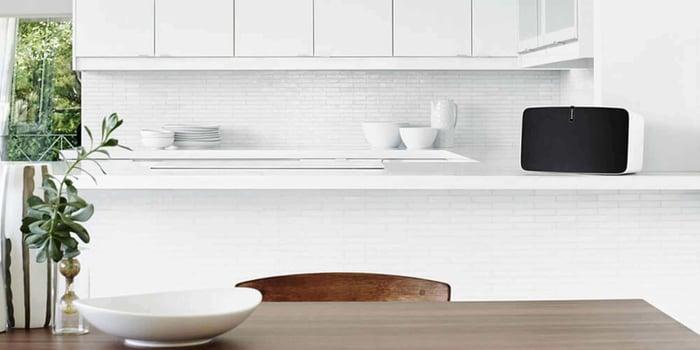 Sonos wireless speaker in a mostly white kitchen.