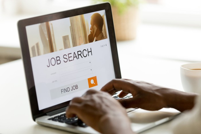 A person sits at a laptop where the screen reads job search.