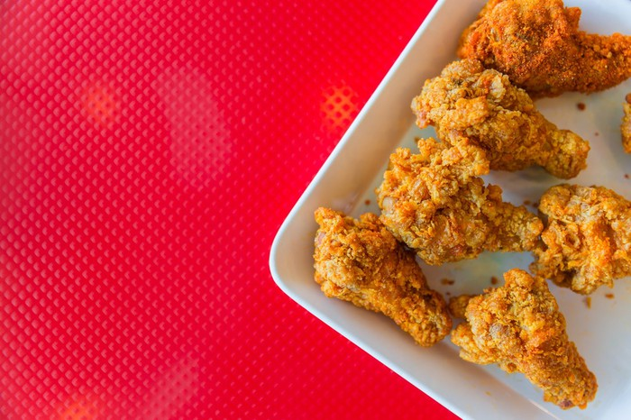 Fried chicken on a plate with a red background.